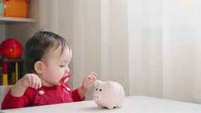 A little girl collects iron coins in a piggy Bank 1920 HD. A little girl collects iron coins in a piggy Bank 1920x1080p HD stock footage