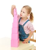 Little girl collects the pink pyramid. Stock Images