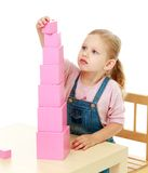 Little girl collects the pink pyramid. Stock Photos