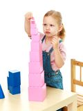 Little girl collects the pink pyramid. Royalty Free Stock Photos