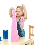 Little girl collects the pink pyramid Royalty Free Stock Photo