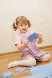 Little girl collects puzzles in a room Stock Photo