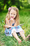 Little girl with color pencils in a park Stock Photography