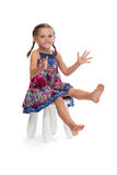 Little girl in a colored dress on a chair Royalty Free Stock Photo