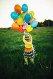 Little girl with colorful balloons stock images
