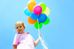 Little Girl With Colorful Balloons. Little girl in front of blue sky, holding colorful balloons Royalty Free Stock Photo