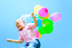 Little Girl With Colorful Balloons. Little girl in front of blue sky, holding colorful balloons Royalty Free Stock Photography