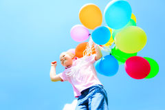 Little Girl With Colorful Balloons. Little girl in front of blue sky, holding colorful balloons Stock Photos