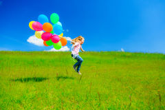 Little Girl With Colorful Balloons. Little girl on green meadow, holding colorful balloons Stock Image