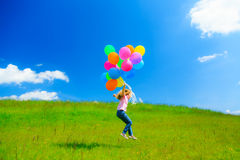 Little Girl With Colorful Balloons. Little girl on green meadow, holding colorful balloons Royalty Free Stock Image