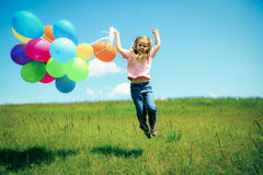 Little Girl With Colorful Balloons. Little girl on green meadow, holding colorful balloons Royalty Free Stock Photography