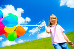 Little Girl With Colorful Balloons. Little girl on green meadow, holding colorful balloons Stock Photo