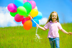 Little Girl With Colorful Balloons. Little girl on green meadow, holding colorful balloons Stock Photography