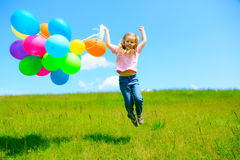 Little Girl With Colorful Balloons. Little girl on green meadow, holding colorful balloons Stock Images