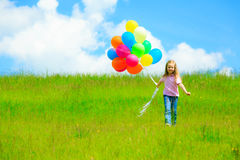 Little Girl With Colorful Balloons. Little girl on green meadow, holding colorful balloons Royalty Free Stock Images