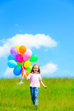 Little Girl With Colorful Balloons. Little girl on green meadow, holding colorful balloons Royalty Free Stock Photos