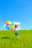 Little Girl With Colorful Balloons. Little girl on green meadow, holding colorful balloons Royalty Free Stock Photo