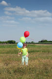 Little girl with colorful balloons on meadow Royalty Free Stock Images