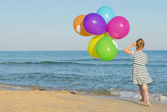 Little girl with colorful balloons. Little girl running with colorful balloons Royalty Free Stock Images