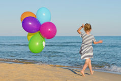 Little girl with colorful balloons. Little girl running with colorful balloons Stock Photo