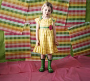 Little girl in colorful dress & boots. A little girl wearing a colorful summer dress and green rain boots Royalty Free Stock Image