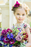 Little girl in colorful dress and flowers. Stock Photo