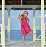 Little girl in colorful dress jumping and dancing on the white wooden pier near the ocean. Stock Photos