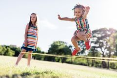 Little girl in a colorful dress jumping through the elastic. royalty free stock image