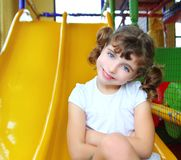 Little girl in colorful playground yellow slide Stock Images