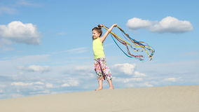 Little girl with colorful ribbons on beach stock footage