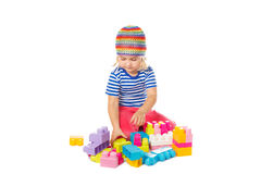 Little girl in a colorful shirt playing with construction toy b Stock Photo