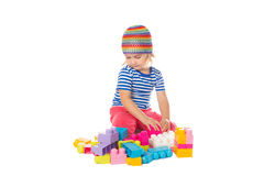 Little girl in a colorful shirt playing with construction toy b royalty free stock images