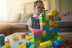 Little girl in a colorful shirt playing with construction toy blocks building a tower Stock Photo