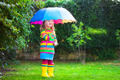 Little girl with colorful umbrella playing in the rain. Kids play outdoors by rainy weather in fall. Autumn fun for children. Toddler kid in raincoat and boots Royalty Free Stock Photography