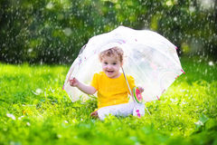 Little girl with colorful umbrella playing in the rain. Kids play outdoors by rainy weather in fall. Autumn outdoor fun for children. Toddler kid outside in Stock Photos