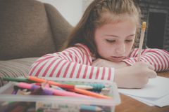 Little girl coloring on blank paper in living room Stock Image