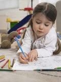 Little Girl Coloring Book On Floor Stock Photos