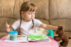 Little girl coloring drawings sitting at the table, child development Royalty Free Stock Photo
