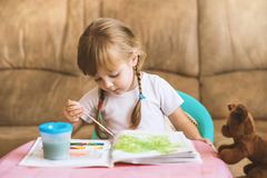 Little girl coloring drawings sitting at the table, child development Stock Photography