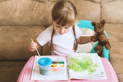 Little girl coloring drawings sitting at the table, child development Royalty Free Stock Photos