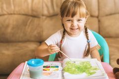 Little girl coloring drawings sitting at the table, child development Stock Photos