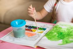 Little girl coloring drawings sitting at the table, child development Stock Photo