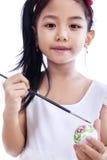 Little girl coloring an easter egg Stock Photos