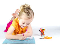 Little girl coloring a rainbow. On white background Royalty Free Stock Photos