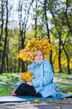 Little girl with colourful autumn headdress. Of bright yellow leaves that she has collected in the park Royalty Free Stock Image