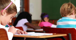 Little girl colouring in the classroom and smiling at camera. In elementary school stock footage