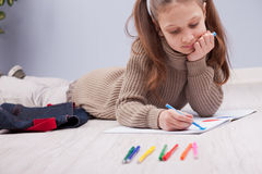 Little girl colouring on her notebook Stock Image