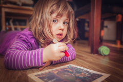 Little girl colouring. Little girl lying on the floor at home and drawing and colouring picture using water pen Royalty Free Stock Image