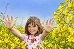 Little girl with colza flower. A happy little girl on a field with colza Royalty Free Stock Photos