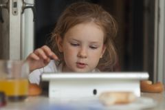 The little girl combines breakfast and games on a tablet. stock images